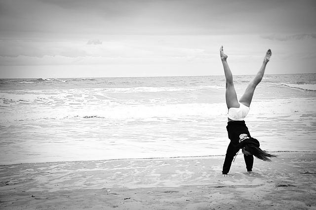 Frau macht Handstand am Strand