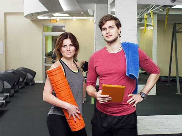 Paar mit Sportkleidung für Übungen mit der Faszienrolle.