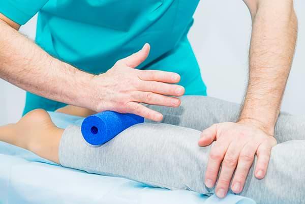 Faszientherapie mit Faszienrolle durch Therapeut bei muskulären Schmerzen an der Wade.